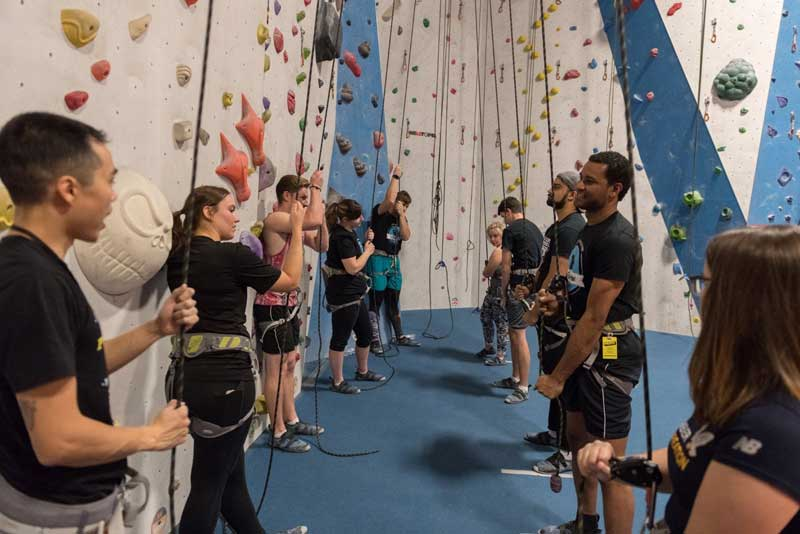 Students geared up in front of rockclimbing wall